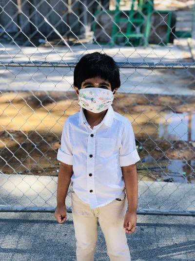 Portrait of boy standing by chainlink fence