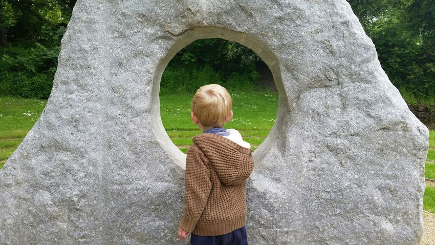 Boy Looking at Stone Sculpture . Cardigan Stone - Object Blonde Caucasian Rear View Toddler  Children Only Outside Outdoors Childhood Exploring Trees Nature Man Made Structure Colour Image Horizontal One Boy Only Pattern Human Hair Building Materials Looking Through