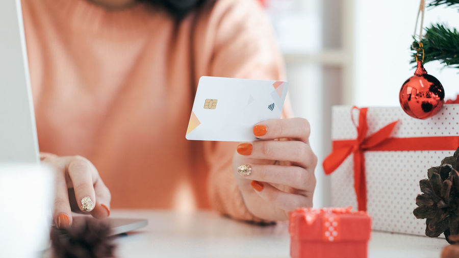 Midsection of woman holding credit card with christmas decoration on table