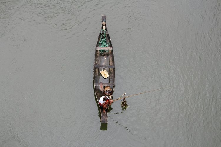 High angle view of man fishing while sitting on boat in lake