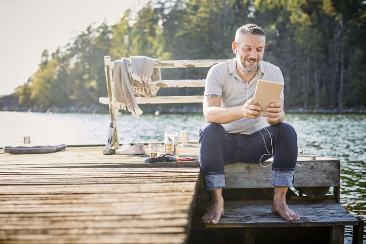 Full length of man using mobile phone while sitting on wood