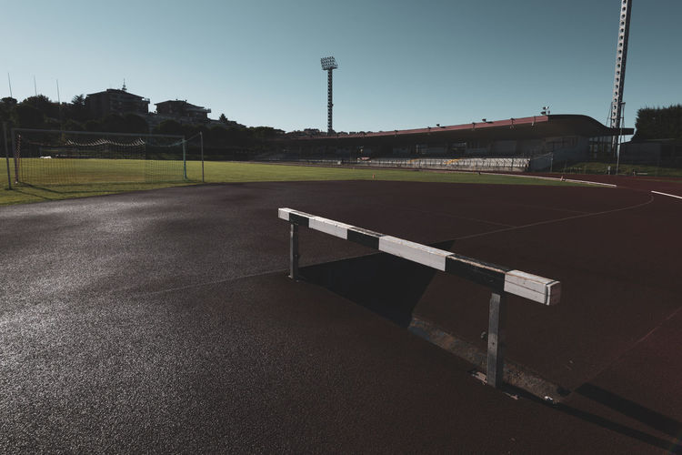 stadium running track hurdle Tartan Track Athletics Sport Running Stadium Competition Speed Lanes Hurdle Hedge Obstacles Wooden Soccer Lighting Equipment Floodlight Field Outdoors Clear Sky Grass Playing Field Nature Empty Absence Day Seat