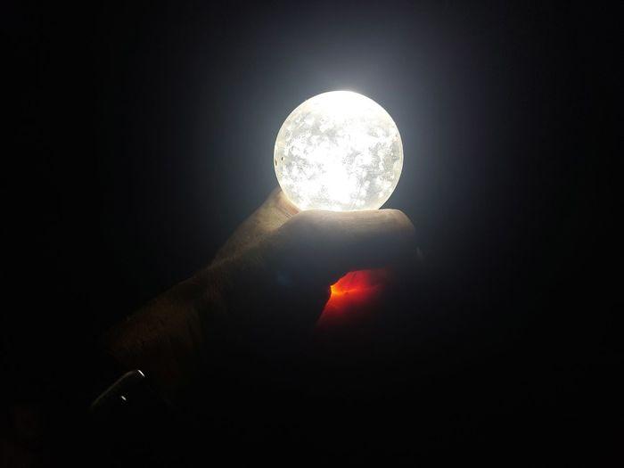 Person holding illuminated light bulb against black background