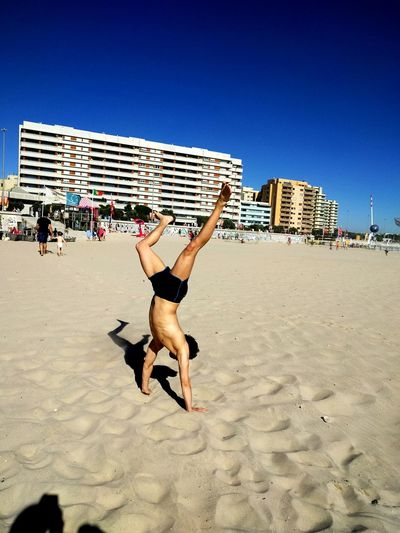 Full length of shirtless man doing handstand on sand at beach against blue sky