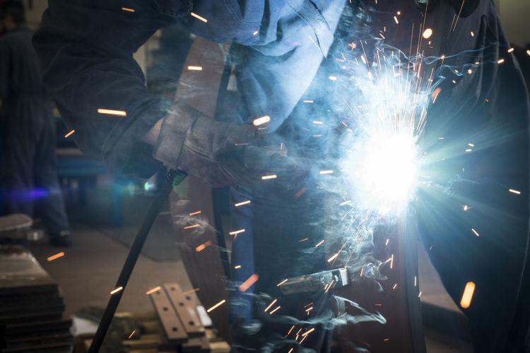 Midsection of welder welding metal in factory