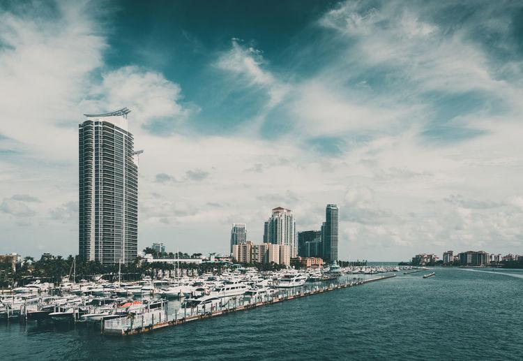 Modern buildings by sea against sky