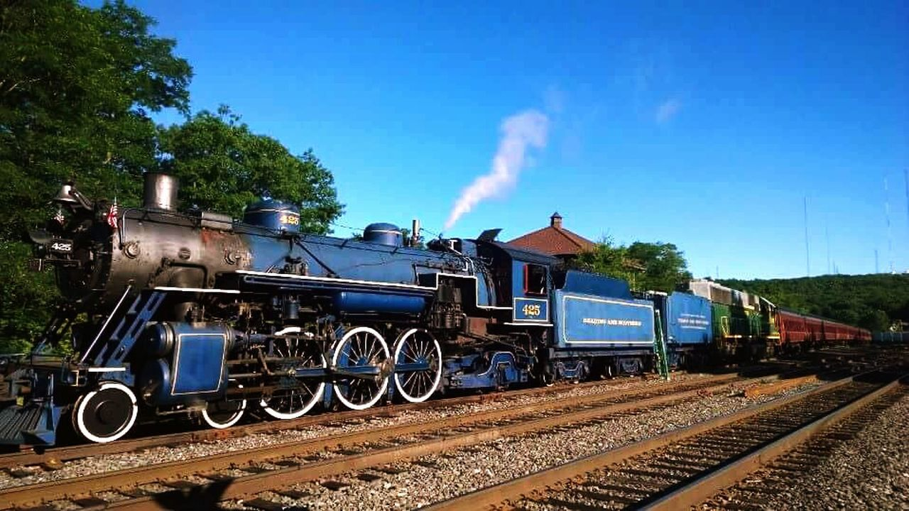 transportation, rail transportation, train - vehicle, railroad track, mode of transport, steam train, locomotive, outdoors, day, sky, smoke - physical structure, freight transportation, sunlight, no people, travel, blue, tree, history, clear sky