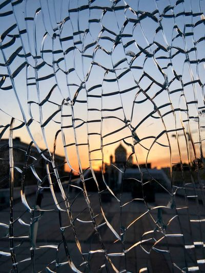 People seen through chainlink fence against sky during sunset