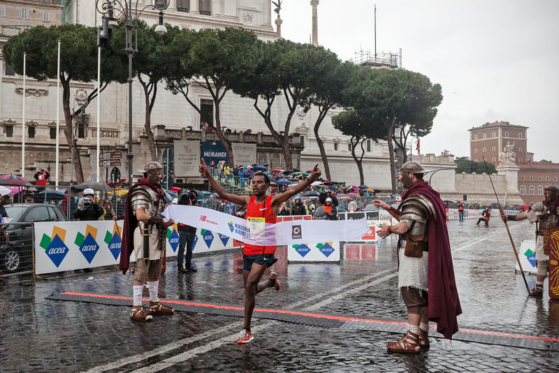 """Rome, Italy - March 22, 2015: Abebe Degefa, winner of the Rome Marathon 2015 meter crosses the finish line with a time of 2h12'23 """". Athlete Atletic Champion City Street Competition Day Finish Line  First Gladiator Italy Marathon Outdoors Rain Roman Rome Runners Running Street Running Water Winner"""