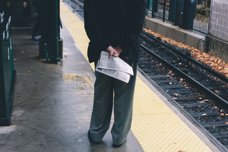 Low section of man holding newspaper while standing at railroad station platform