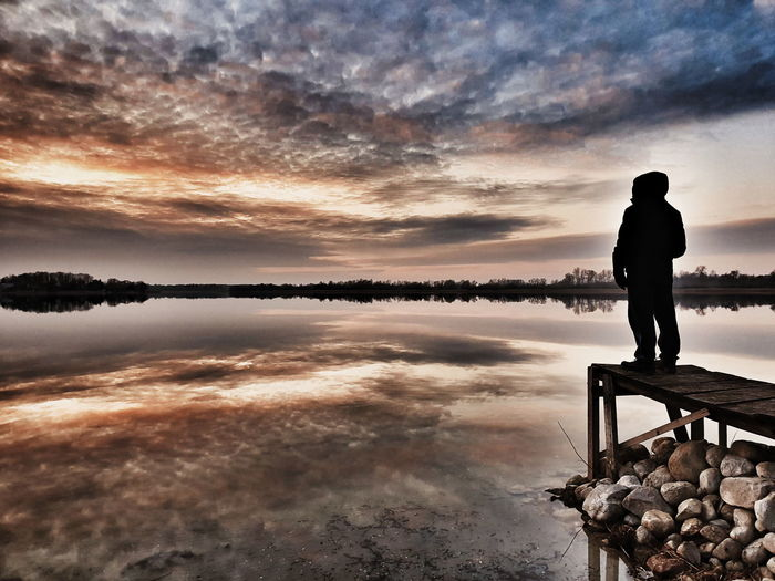 Man standing on lake against sky during sunset