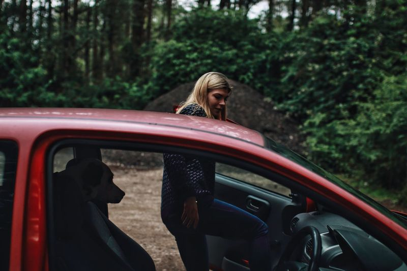 Side View Of Woman Sitting In Car At Forest