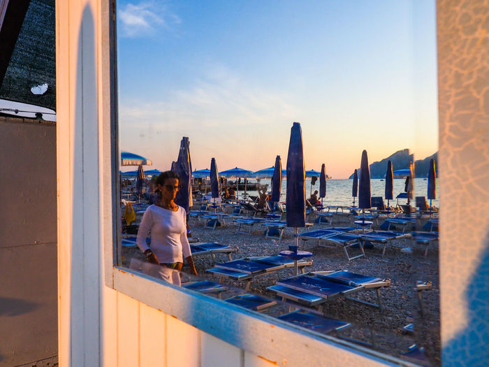 Mirror reflection of a beach resort at portonovo during summer season at sunrise while a lady walks on the opposite site od 18 august 2018, Italy Beachphotography Italy❤️ Italy Marche Marche Region Blue Sky Sea Sea And Sky Seaside Mirror Mirror Reflection Beach Resort View Beachphotography Portonovo Sunset Sky Coast Shore