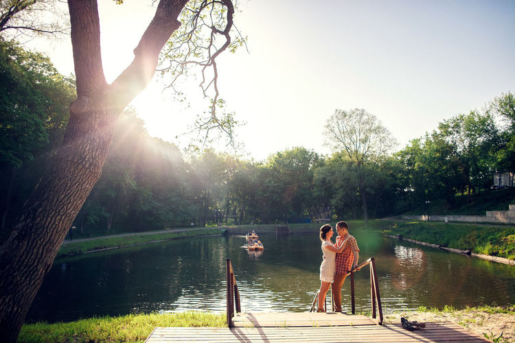 couple relax in park with lake at sunset. Summer time. Couple enjoy time together. Authentic couple at countryside. Togetherness Outdoors Lake Countryside Village Couple - Relationship Relaxing Relaxation Lifestyles Summer Sunset Authentic Authentic Moments Relationship Springtime Tree Real People Plant Nature Sunlight Leisure Activity Two People Lake Side Females Lake View