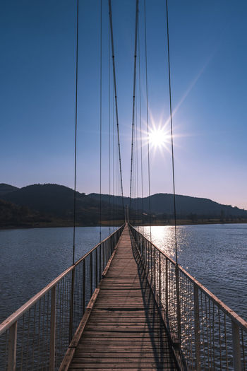 The longest suspension bridge in Bulgaria over Studen Kladenez dam with distance between the two towers of 260m. The only way to reach Lisicite village Reflection Water Sunset Nature Sky Bridge Travel Tower Lake Mountain Direction Pylon Way Suspension Dam Bulgaria Metal Overcast Wooden Suspension Bridge Longest Warm Clothing Sunlight Beauty In Nature Tranquility Railing Tranquil Scene Scenics - Nature Connection Pier Sun No People The Way Forward Wood - Material Built Structure Outdoors Lens Flare Sailboat