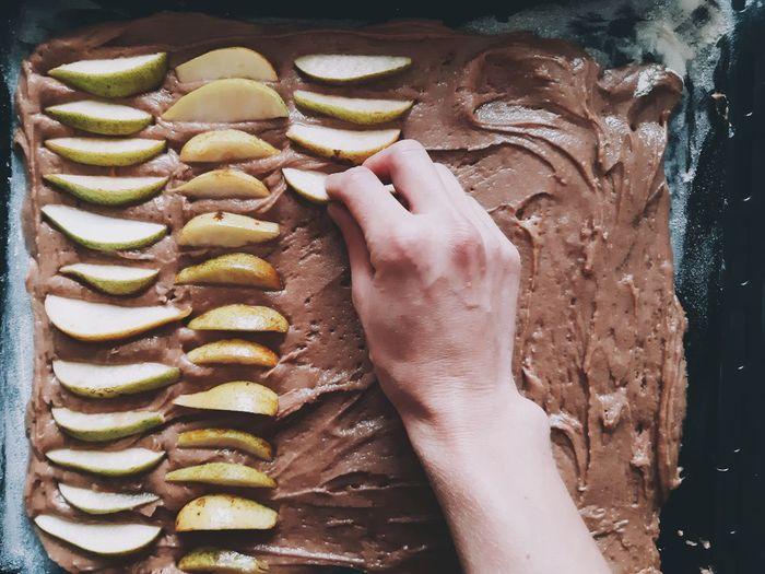 Close-up of hand preparing pear cake