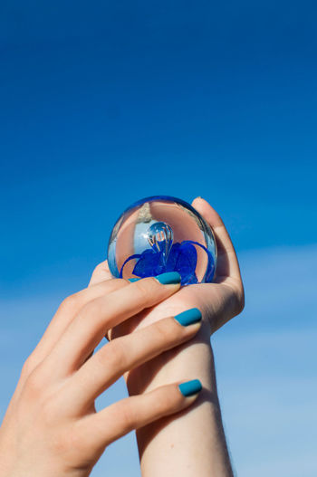 Cropped hands of woman holding crystal ball against blue sky