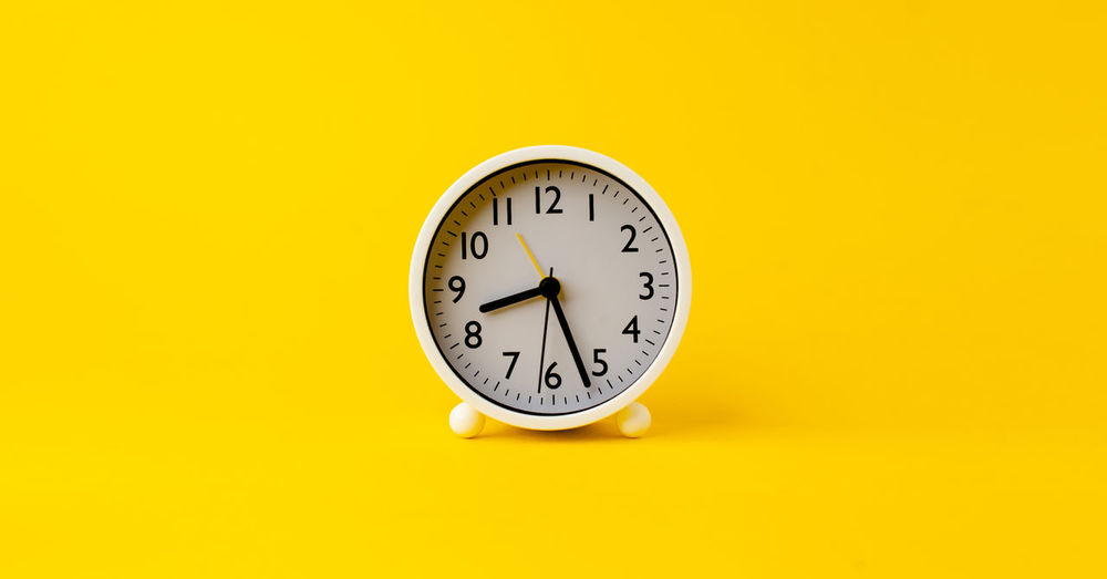 Close-up of clock on yellow background