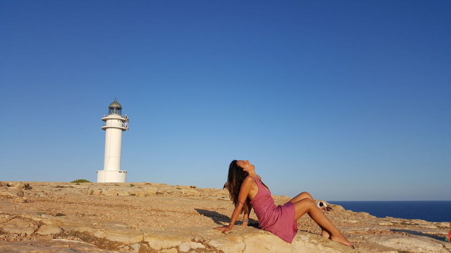 Side View Of Woman Sitting At Beach Against Lighthouse And Clear Blue Sky