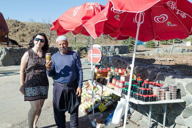 Golan Heights, Israel, August 27, 2017 : The seller - druz stands near his shop with canned sweets in the parking lot, on Mount Bental., on the Golan Heights in Israel. Agriculture Druze Golan Heights Happy Middle East Sale Travel Buyer Day Food Fresh Fruit Galilee Healthy Israel Mount Bental Mountain Organic Outdoors People Seller Store Summer Sweet Tourism