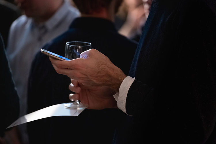 Refreshment Drink Glass Holding Food And Drink Midsection Alcohol Lifestyles Leisure Activity Adult Real People Indoors  People Human Hand Focus On Foreground Hand Close-up Suit Wine Smart Phone Business Businessman Communication Meeting Togetherness
