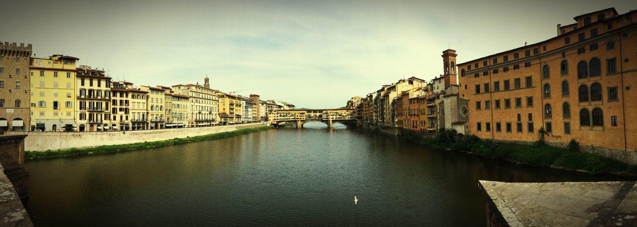Ponte Santa Trinita Bridge Over Arno River Amidst Buildings Against Sky
