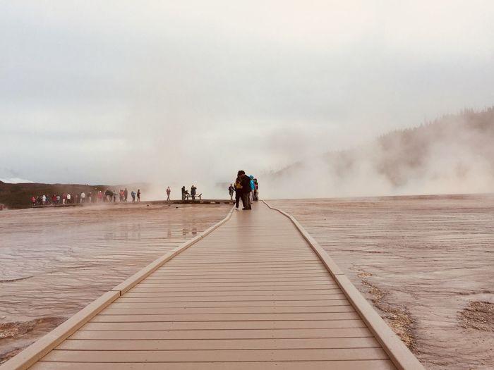 People on boardwalk at hot spring against sky