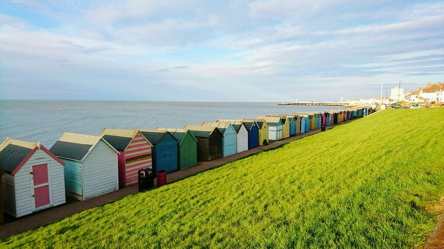 Beach huts in a row against calm sea