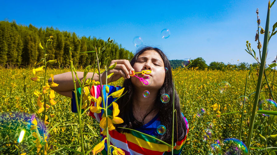 Girl blowing bubbles on field during sunny day