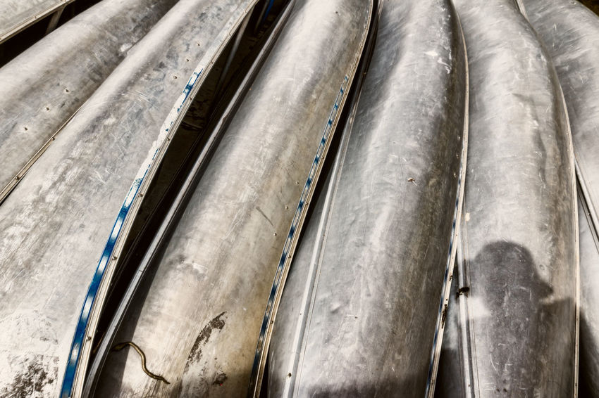 Some old beat up canoes for rent waiting for customers Aluminium Aluminum Beat Up Canoes Close-up Day Dented No People Reflection Wide Angle Worn