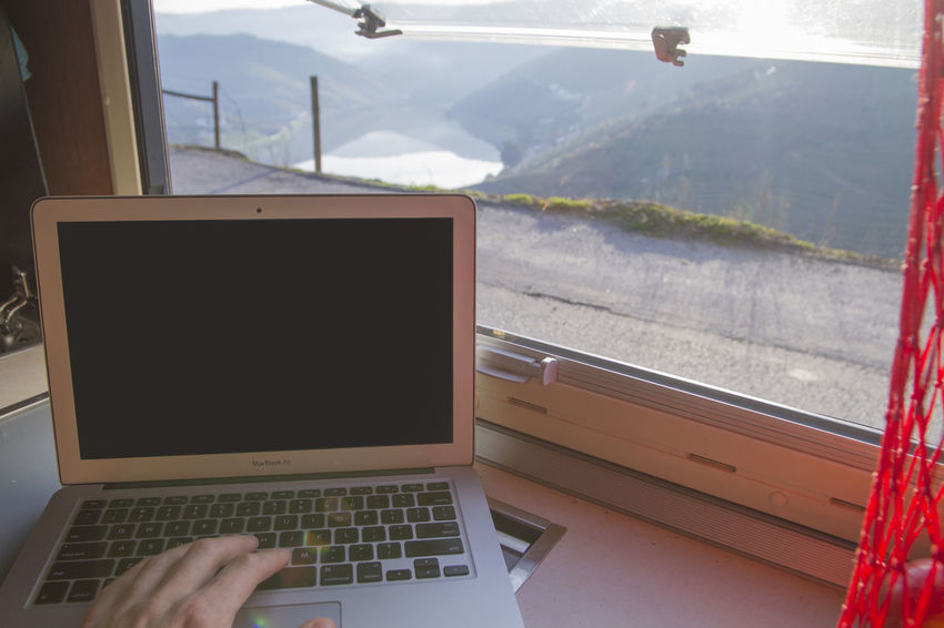 Working on laptop with beautiful view through window of vehicle/motorhome Close-up Day Human Body Part Human Hand Indoors  Laptop Mountain Mountain Range Nature One Person People Real People Sky Technology Transportation Using Laptop Window Wireless Technology