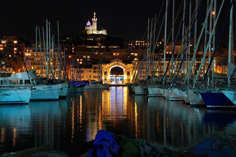 Boats moored at old port of montreal in illuminated city