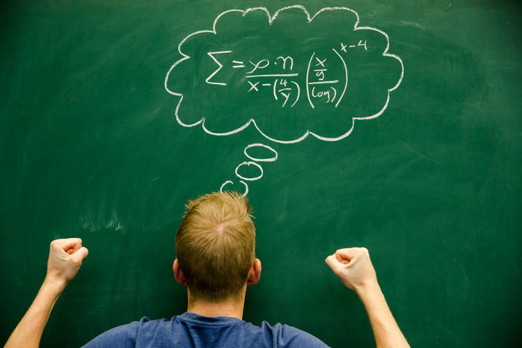 Rear view of man gesturing while standing by formula on blackboard