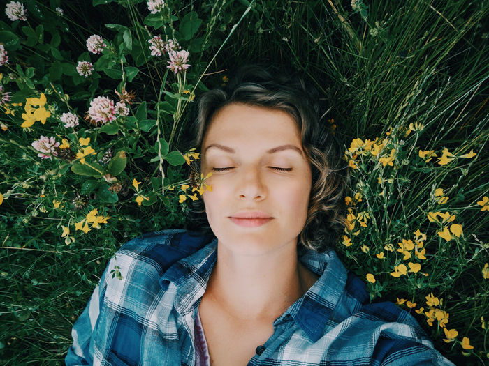 Portrait of young woman lying down on plant