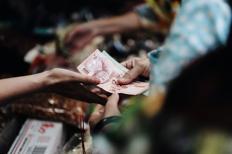 Cropped hands of costumer giving paper currency to vendor at market