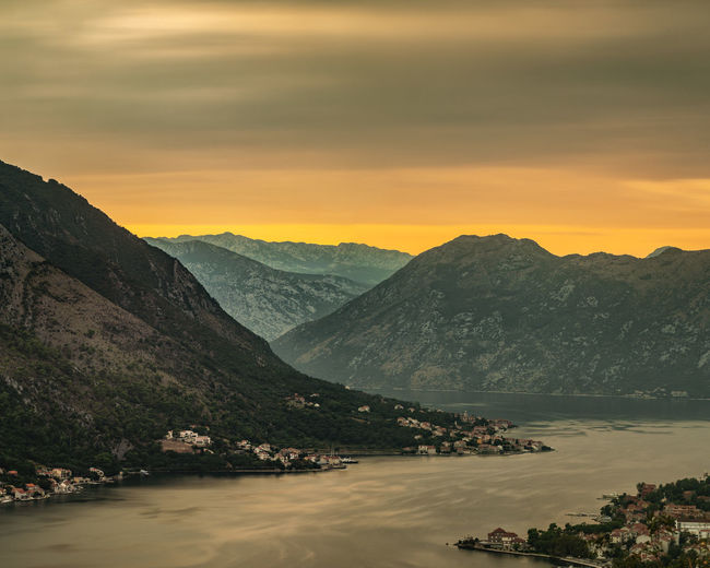 Scenic view of river by mountains against sky during sunset