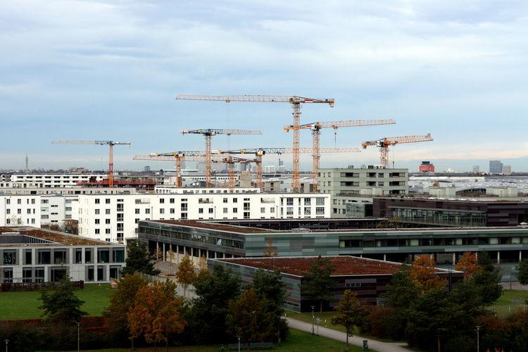 Cranes by buildings against sky in city