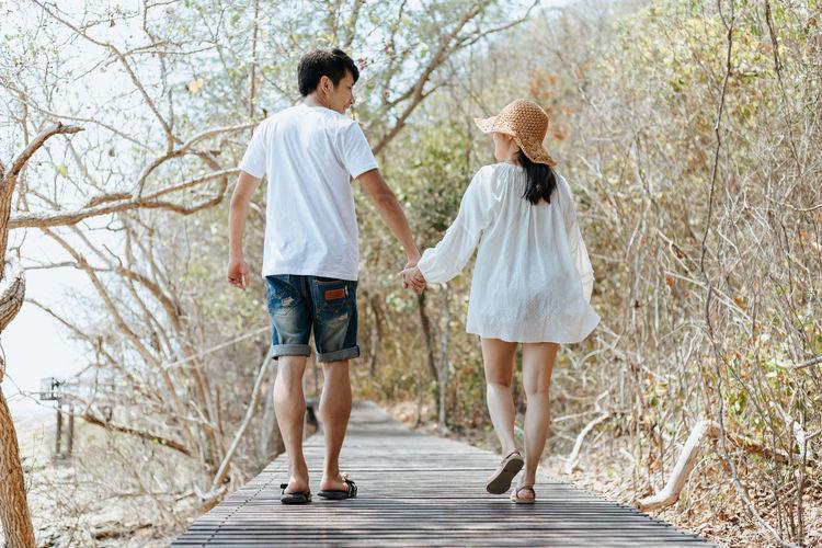 Rear view of couple walking along plants