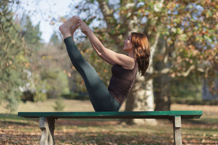 Woman sitting on bench in park