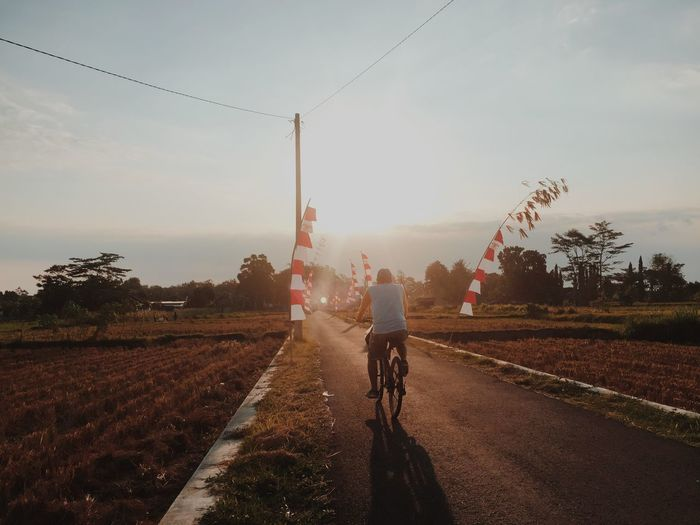17.62° Transportation Sky Bicycle Field Road Rear View Landscape Mode Of Transportation Riding Real People Land Land Vehicle Nature One Person Ride Rural Scene Environment Direction Men Day The Way Forward Outdoors