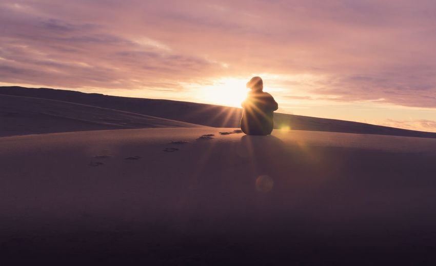 Man On Sand Dune Against Sky During Sunset