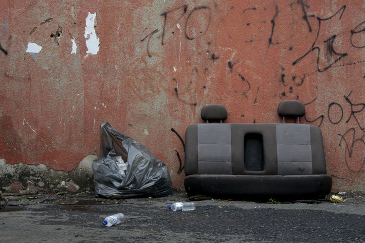 Garbage bin against wall in city
