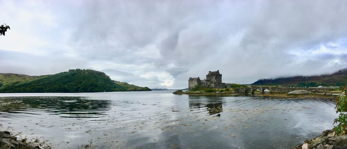 Castle by lake against cloudy sky
