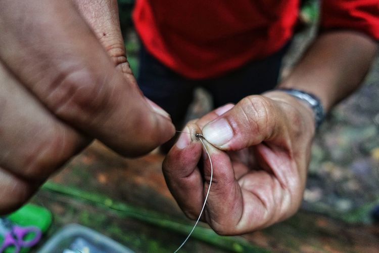 Low section of man preparing fishing tackle