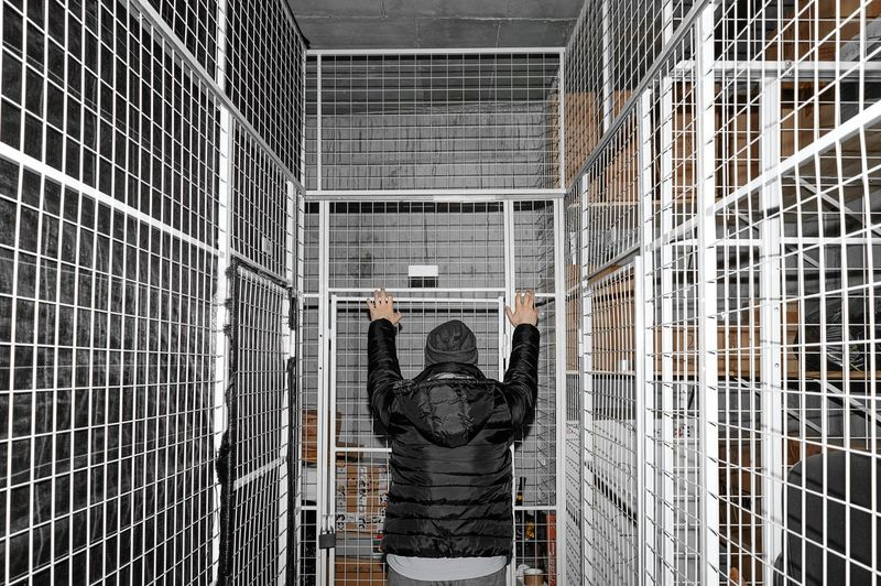 Rear view of a man standing against fence in room
