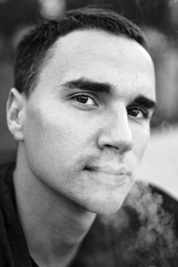 Close-up portrait of young man exhaling smoke