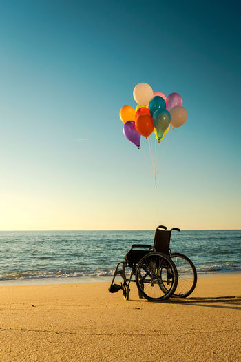 Silhouette wheelchair with colorful balloons on beach against clear blue sky during sunset