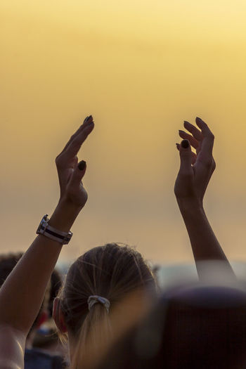 Close-up of woman arms raised against clear sky during sunset