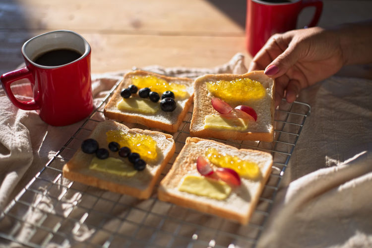 Breakfast Food And Drink Berry Fruit Bread Breakfast Coffe Cup Cup Drink Food Food And Drink Freshness Fruit Hand Holding Human Body Part Human Hand Indoors  Jam Lifestyles Meal Mug One Person Preparation  Preparing Food Real People Selective Focus Table Toasted Bread