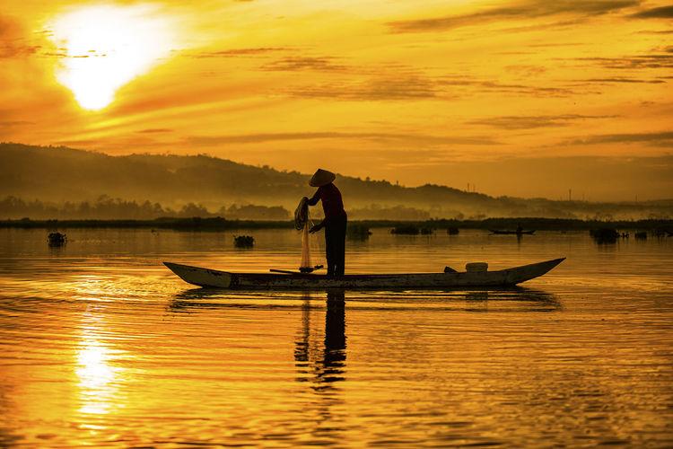 Silhouette fisherman fishing at lake against orange sky